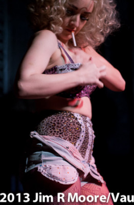 Photo of performer at Bushwick Burlesque, in funky top and tiny shorts, ripped fishnets, with a cigarette dangling from her mouth, digging in her bra for a light.