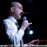 Photo of blockhead Donny Vomit talking into the microphone at Bushwick Burlesque with a giant screw in his nose.