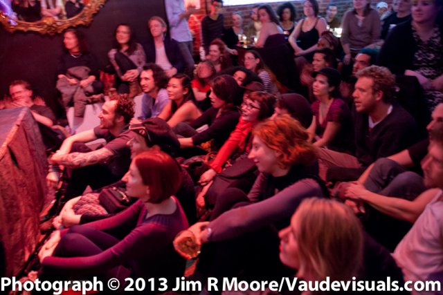 Photo of the audience at Bushwick Burlesque - the house is packed and people are sitting on the floor.