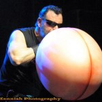 Sideshow performer Adam the First Real Man in black tank and shades looks like he's blowing up a giant balloon that look like a butt, at the 2013 Coney Island Spring Gala.