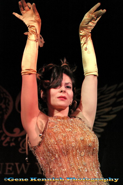 Burlesque performer Albadoro Gala in gorgeous gold beaded dress with fringe and gold gloves, holds her arms up elegantly over her head at Joe the Shark's Sharkbite Sideshow.