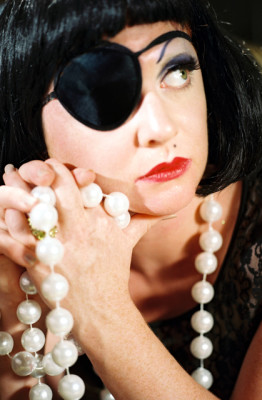 Miss Astrid headshot, eyepatch on her right eye, with a long strand of large pearls clasped in her hands.