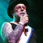 Mayor of Coney Island Dick Zigun in tank top and black hat, holds the microphone up as he speaks, his whole bare arm covered in tattoos, at the 2013 Coney Island Spring Gala.