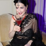 Dita Von Teese wearing custom black lace sari by Shivan and Narresh, sipping a cointreau cocktail
