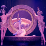 Dita Von Teese is on her back in a giant open ladies' compact prop, with the mirror facing the audience, her leg kicked up, with the Vontourage girls standing on each side.