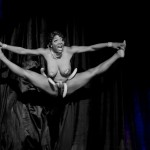 A black and white photo of Perle Noire doing her famous split in the air, in pasties and panties and a belt of bananas around her waist.