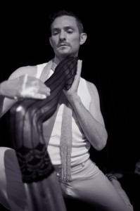 Monsieur Romeo caresses a mannequin's leg dressed in lace stockings.