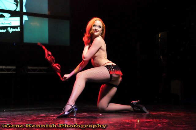 Burlesque performer Gal Friday kneels on one knee in black and red briefs, hose and heels, and yanks off her bra in one feel swoop, at the Coney Island USA Spring Gala.