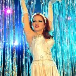 Burlesque performer Jo Weldon in white dress with fringe skirt and white gloves, arms up over her head, in front of a tinsel curtain, at the 2013 Coney Island Spring Gala.