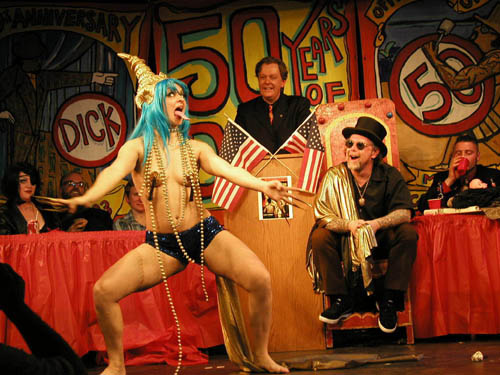 Julie Atlas Muz performing in black boy shorts and a blue wig for Dick Zigun at his 50th Birthday Party on the Coney Island Sideshow stage.
