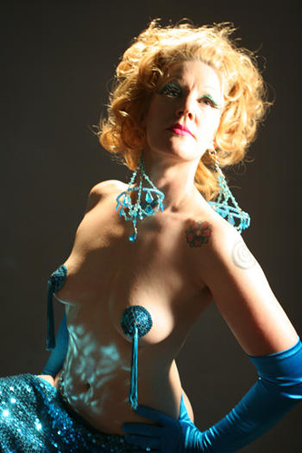 Burlesque performer Paula the Swedish Housewife in blue pasties and satin gloves, poses for photographer Don Spiro, with blue chandelier earrings dangling from her ears.