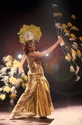 Burgundy Brixx swings stunning yellow and white feather fans, wearing a golden gown and headpiece, Toronto Girlesque.