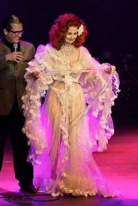 Mysterion helps Tempest Storm up to the stage at the Toronto burlesque show, Girlesque. She is dressed in a beautiful frilly sheer robe.