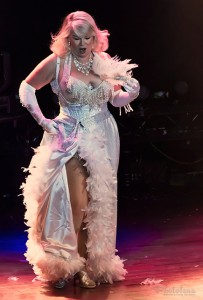 Tiffany Carter in all white, in a white bra and corset covered in beautiful beaded fringe, gold and silver accents, taking a long accent feather out of her hair, at the Toronto burlesque show, Girlesque.