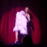 burlesque performer with white feathers onstage at the premiere Prague Burlesque Show