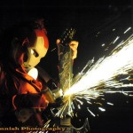 Sideshow performer Serpentina in robot mask, welding a guitar, at the Coney Island USA 2013 Spring Gala.
