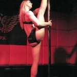 Performer Shaina Cruea in black bra and panties does a full split on the pole at Joe the Shark's Sharkbite Sideshow.