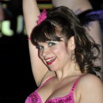 Burlesque performer Tiny D smiles in a bright pink beaded corset, with her right arm up in the air, at the Coney Island USA 2013 Spring Gala.